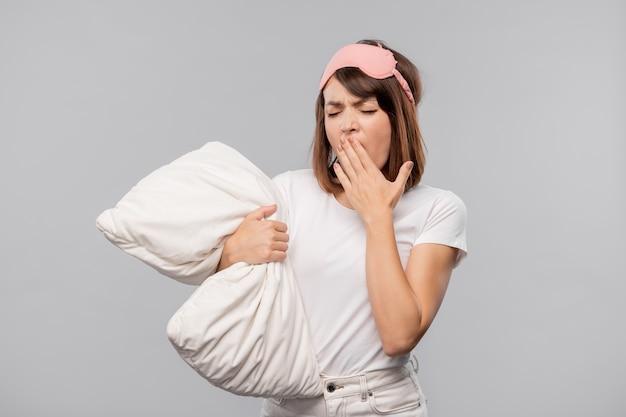 Junge brünette frau in nachtwäsche und maske, die ihren mund bedeckt, während sie isoliert gähnt