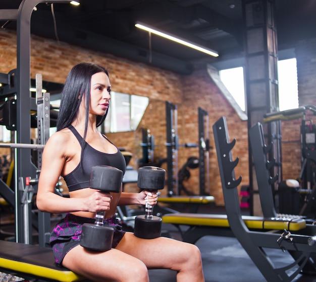 Junge brünette frau in sportbekleidung mit hanteln in ihren händen sitzt auf einer bank im fitnessstudio.