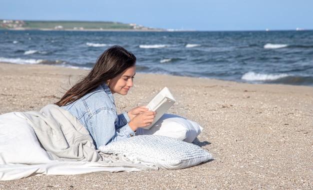 Junge brünette frau liegt am meer am strand mit einer decke bedeckt und liest ein buch. gemütliche atmosphäre am strand, sommerkonzept.
