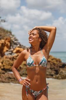 Junge brünette frau mit buntem bikini im sommer am strand