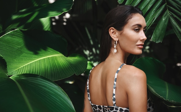 Junge brünette frau mit gebräunter haut, einen bikini tragend, in der nähe von palmendschungelblättern stehend und beiseite schauend.