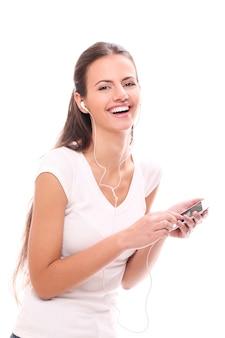 Junge brünette frau mit kopfhörern und smartphone
