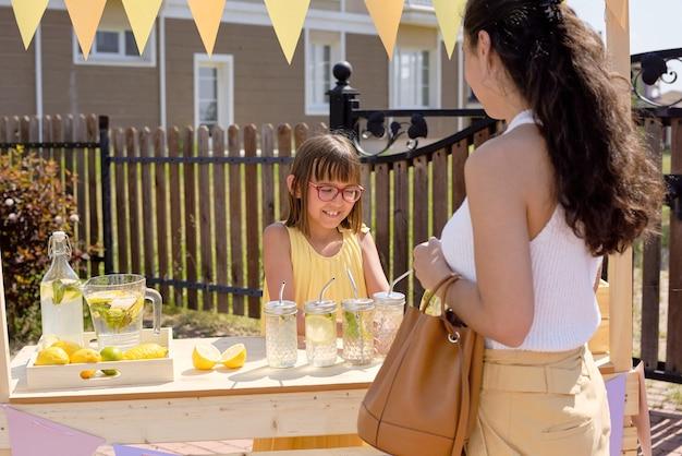 Junge brünette frau mit langen haaren, die glas der frischen hausgemachten limonade wählt, die durch niedliches kleines mädchen durch stall am heißen sommertag verkauft wird