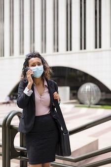 Junge brünette frau mit medizinischer maske, die ein telefongespräch im freien führt. unternehmenskonzept.