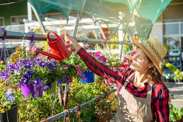 Junge brünette frau mit strohhut in einem blumengewächshaus kümmert sich um pflanzen mit liebe und hingabe