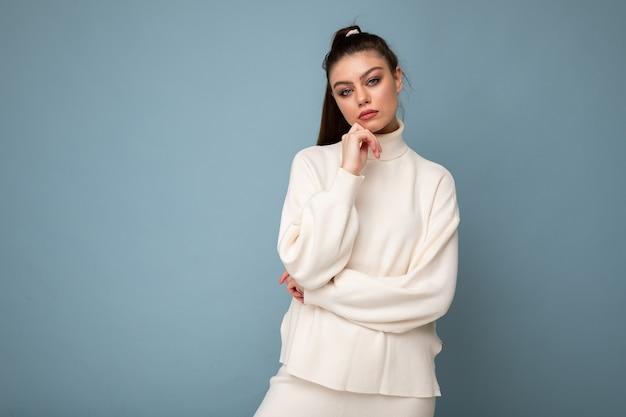 Junge brünette frau mit weißem casual-pullover auf blauem hintergrund isoliert suchen