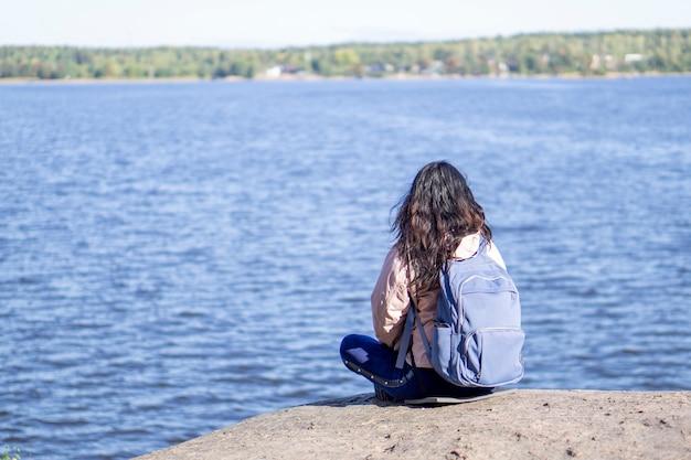 Junge brünette frau sitzt mit dem rücken zur kamera, rucksack hinter ihren schultern und betrachtet das panorama des sees. konzept der entspannung in der natur