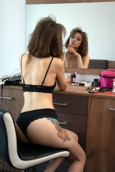 Junge brünette frau sitzt morgens in ihrem schlafzimmer vor dem spiegel und ist gerade aufgewacht