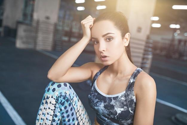Junge brünette frau trainiert im fitnessstudio müde sitzend auf einer kiste mit kaltem wasser gelehnt