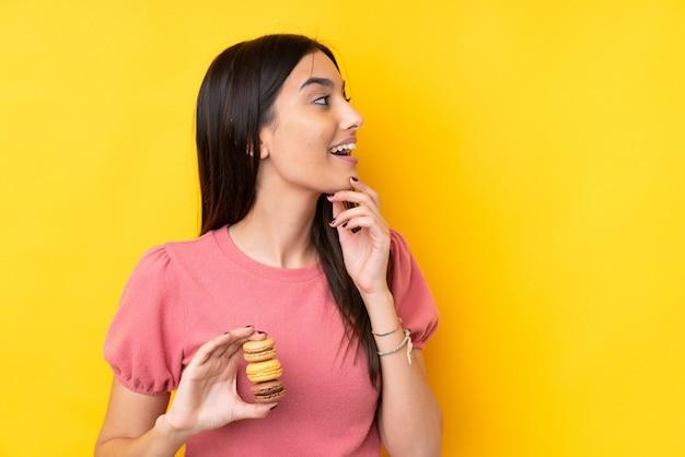 Junge brünette frau über gelb, die bunte macarons hält und eine idee denkt