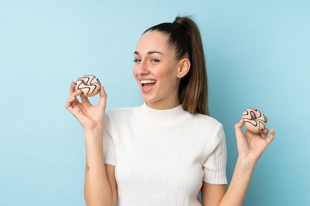 Junge brünette frau über isolierte blaue wand, die donuts mit glücklichem ausdruck hält