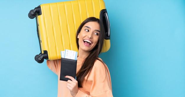 Junge brünette frau über isolierte blaue wand im urlaub mit koffer und pass