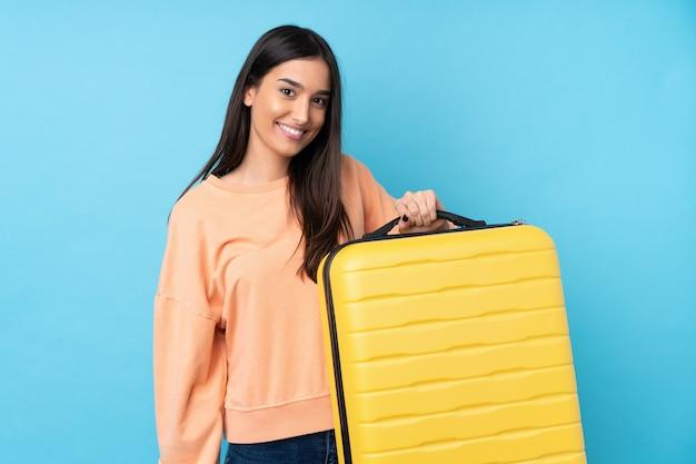 Junge brünette frau über isolierte blaue wand im urlaub mit reisekoffer und unglücklich