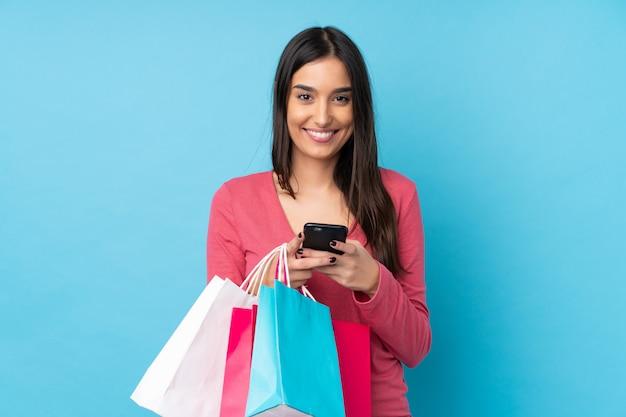 Junge brünette frau über isolierter blauer wand, die einkaufstaschen hält und eine nachricht mit ihrem handy an einen freund schreibt