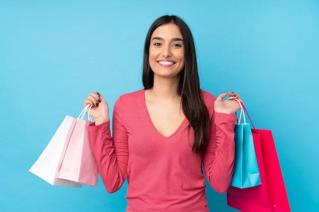 Junge brünette frau über isolierter blauer wand, die einkaufstaschen hält und lächelt
