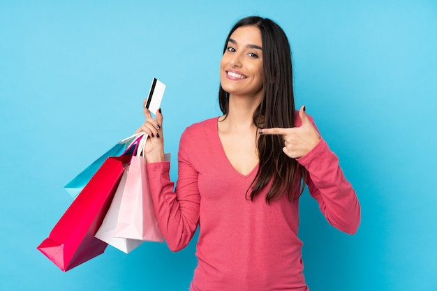 Junge brünette frau über isolierter blauer wand, die einkaufstaschen und eine kreditkarte hält