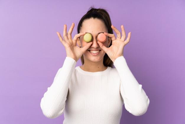 Junge brünette frau über isolierter lila wand, die bunte französische macarons als brille trägt
