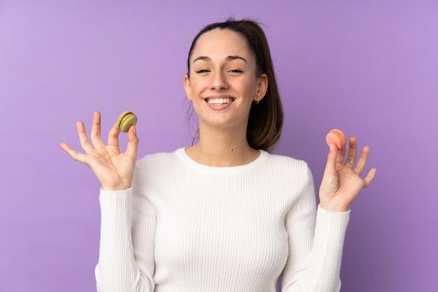 Junge brünette frau über isolierter lila wand, die bunte französische macarons hält