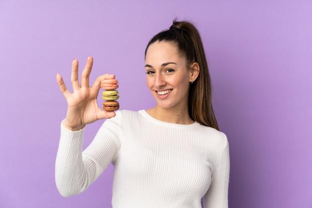 Junge brünette frau über isolierter lila wand, die bunte französische macarons und mit glücklichem ausdruck hält