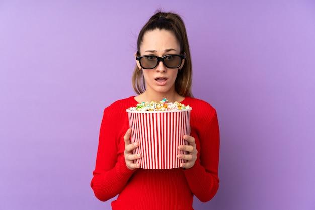 Junge brünette frau über isolierter lila wand überrascht mit 3d-brille und hält einen großen eimer popcorn