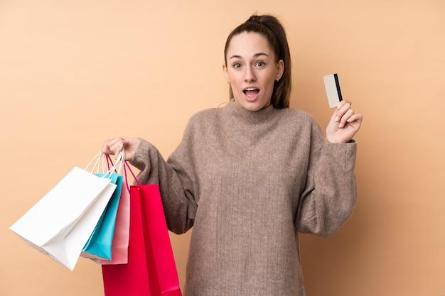 Junge brünette frau über isolierter wand, die einkaufstaschen hält und überrascht