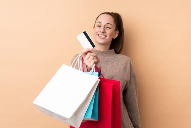 Junge brünette frau über isolierter wand, die einkaufstaschen und eine kreditkarte hält