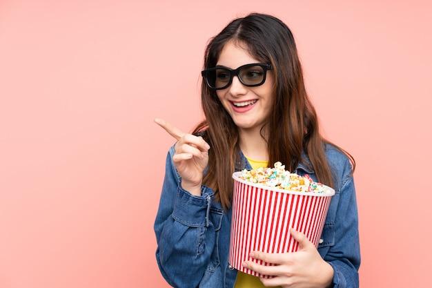 Junge brünette frau über rosa wand mit 3d-brille und hält einen großen eimer popcorn, während sie nach vorne zeigt