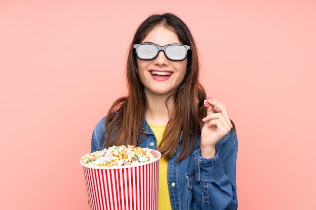 Junge brünette frau über rosa wand mit 3d brille und hält einen großen eimer popcorns