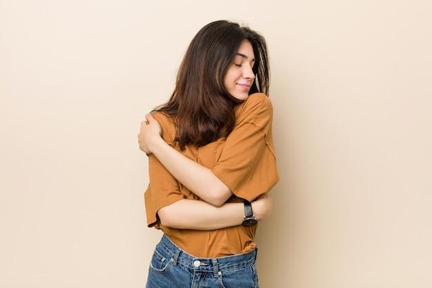 Junge brünette frau umarmt, lächelt sorglos und glücklich