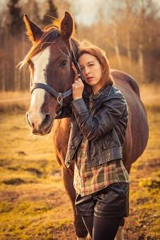 Junge brünette frau und pferd auf herbstnatur