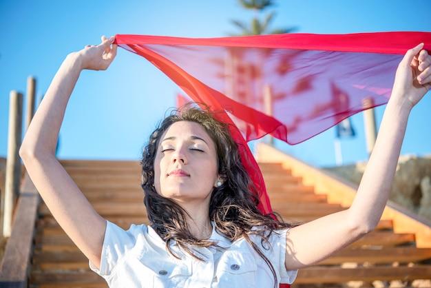Junge brünette frau weiß gekleidet gegen blauen himmelroten schal schließen augen glückliches vergnügen im wind
