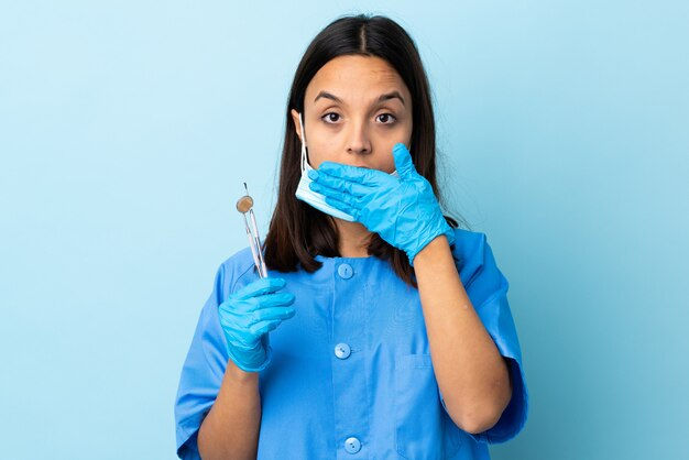 Junge brünette gemischte rasse zahnarztfrau, die werkzeuge über isoliertem wandbedeckungsmund mit händen hält