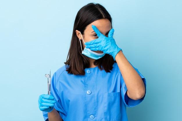 Junge brünette gemischte rasse zahnarztfrau, die werkzeuge über isolierten abdeckenden augen durch hände und lächeln hält