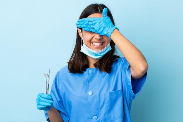 Junge brünette gemischte zahnarztfrau, die werkzeuge über isolierte wand hält, die augen durch hände bedeckt und lächelt