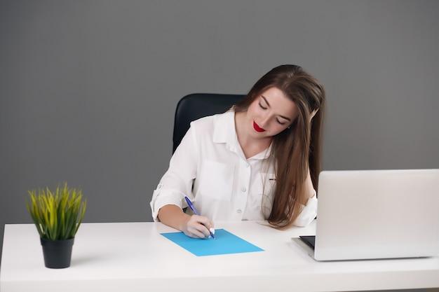 Junge brünette geschäftsfrau, die auf hellem modernem arbeitsplatz sitzt