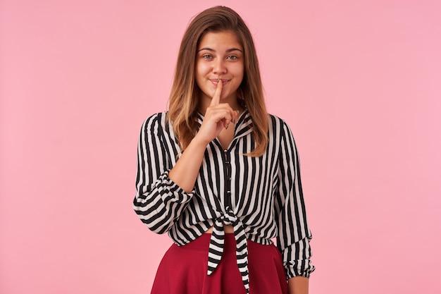 Junge brünette grünäugige frau mit natürlichem make-up, das angenehm lächelt und zeigefinger auf ihrem mund hält, gekleidet in festlicher abnutzung, während sie auf rosa posiert