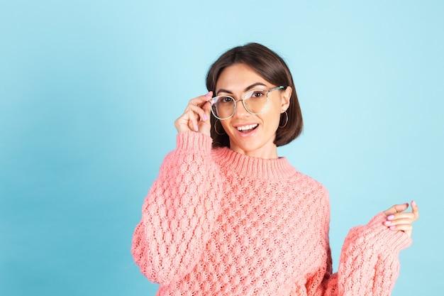 Junge brünette im rosa pullover lokalisiert auf blauer wand