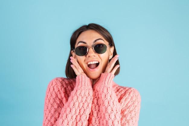 Junge brünette im warmen rosa pullover lokalisiert auf blauer wand