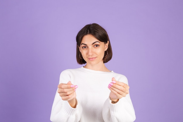 Junge brünette im weißen lässigen pullover lokalisiert auf lila wand