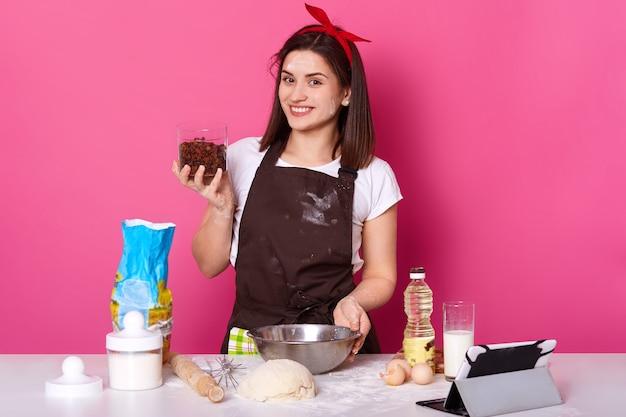 Junge brünette köchin steht an der küche, die behälter mit rosine hält, aufrichtig lächelnd, zutaten in schüssel mischend. die charmante süße positive dame entwickelt ihre kochkünste und probiert ein neues rezept aus.