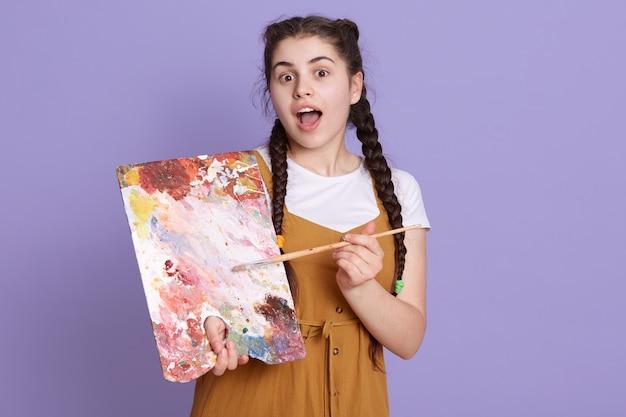 Junge brünette künstlerfrau mit zöpfen, die malerpinsel und -palette über fliederwand halten, posierend mit überraschungsgesicht, stehend mit geöffnetem mund.
