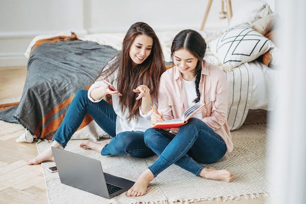 Junge brünette mädchen befreundet studenten im gelegenheitsarbeitsprojekt zusammen auf der suche nach informationen im internet per handy und laptop im zimmer