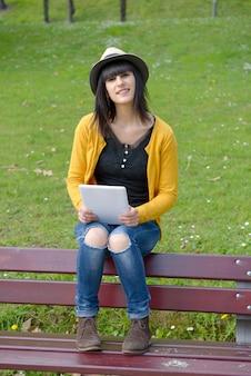 Junge brünette mädchen, die auf einer bank mit einer tablette im park sitzen