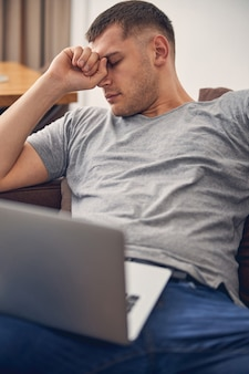 Junge brünette männer schlafen auf dem sofa, während sie den laptop auf den knien halten