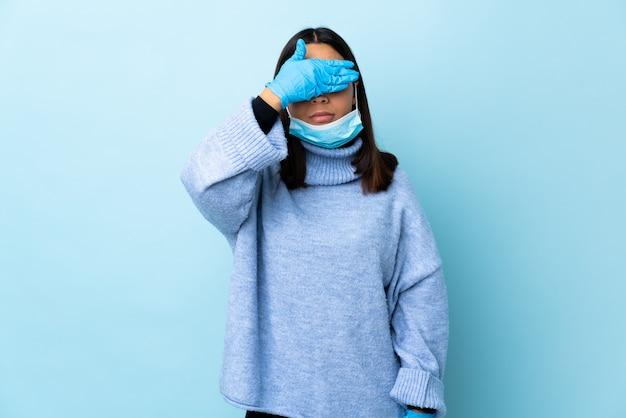 Junge brünette mischlingsfrau, die vor dem coronavirus mit einer maske und handschuhen über isolierter blauer wand schützt, die augen durch hände bedeckt. ich will nichts sehen