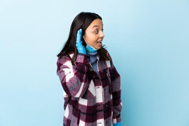 Junge brünette mischlingsfrau, die vor dem coronavirus mit einer maske und handschuhen über isolierter blauer wand schützt, die etwas hört, indem man hand auf das ohr legt
