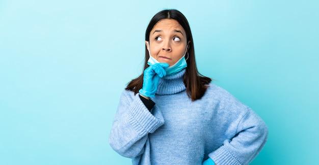 Junge brünette mischlingsfrau, die vor dem coronavirus mit einer maske und handschuhen über isolierter blauer wand schützt, die zweifel und denken hat