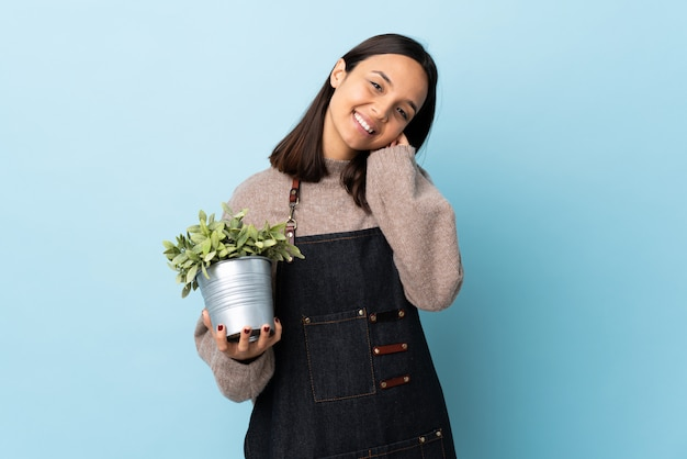 Junge brünette mischrassenfrau, die eine pflanze auf lokalisiertem blauem lachen hält