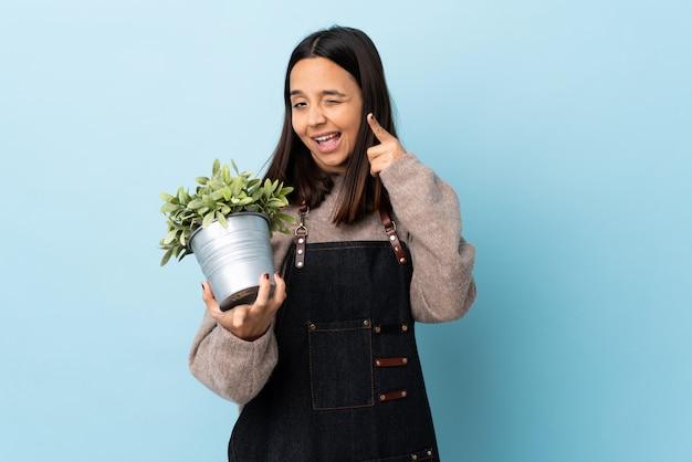 Junge brünette mischrassenfrau, die eine pflanze über der blauen wand hält, die telefongeste macht und nach vorne zeigt.