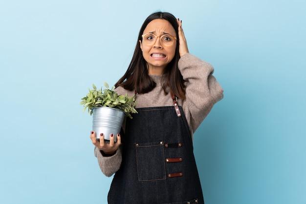 Junge brünette mischrassenfrau, die eine pflanze über isolierte blaue wand hält, die nervöse geste tut